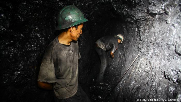 Miners dig in a dark coal mine