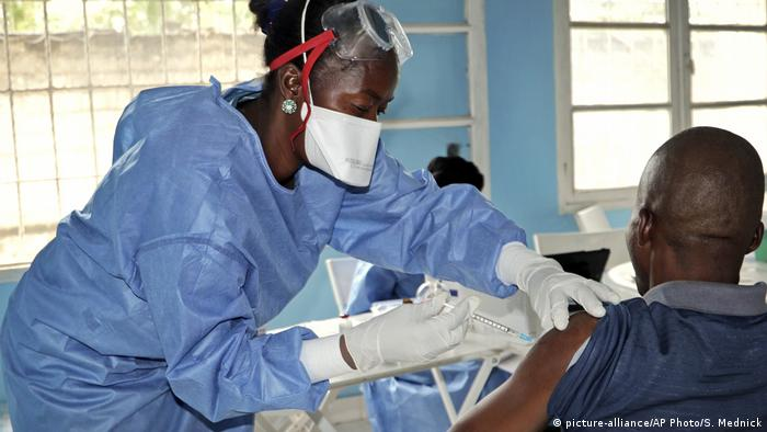 A nurse in blue protective gear and gloves administers a vaccination to a man