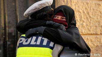 Демонстрация в Копенгагене против запрета на ношение паранджи - женщина в парандже обнимает женщину-полицейского