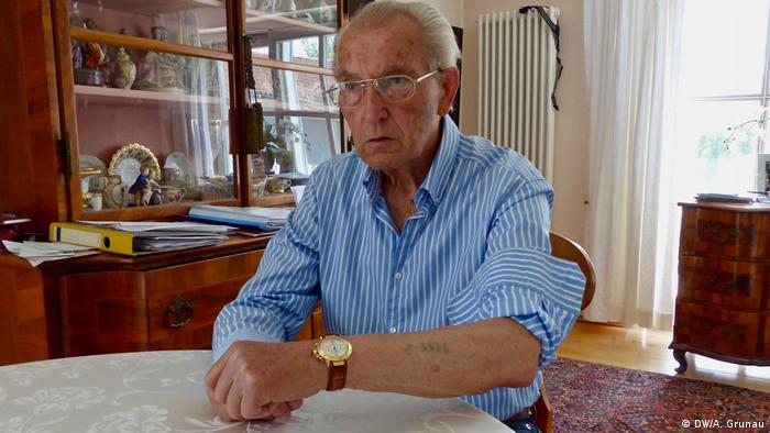 Hermann Mano Höllenreiner sits with his hands crossed on a table