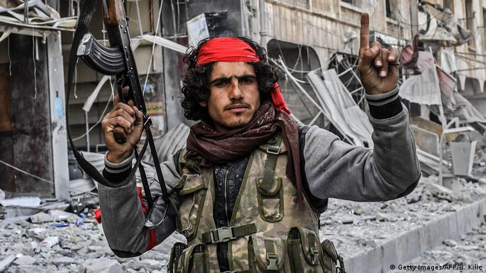 A Turkish-backed Syrian rebel celebrates after capturing Afrin in March