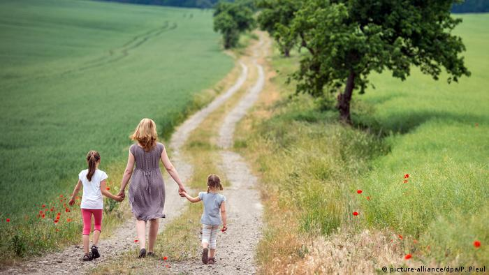 Mother and daughters walking down a grassy path