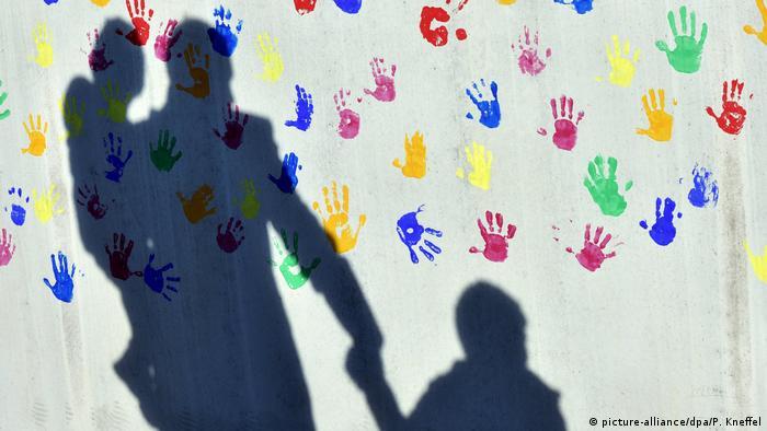 Foto mostra sombra de homem carregando uma criança no colo e dando a mão para outra diante de muro branco pintado com impressões coloridas de mãos de crianças