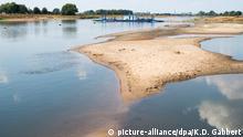 ARCHIV - 30.07.2018, Sachsen-Anhalt, Ronney: Trockengefallene Sandbänke sind in der Elbe zu sehen. Dahinter hat die Elbfähre Elbfähre «Saalhorn Barby» festgemacht. (zu dpa «Niedrigwasser legt Weltkriegsmunition frei - zahlreiche Funde» vom 02.08.2018) Foto: Klaus-Dietmar Gabbert/ZB/dpa +++ dpa-Bildfunk +++ | Verwendung weltweit