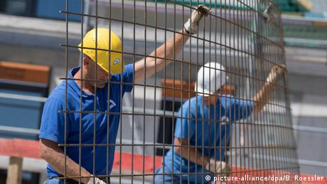 Workers with hard hats carrying fence (picture-alliance/dpa/B. Roessler)