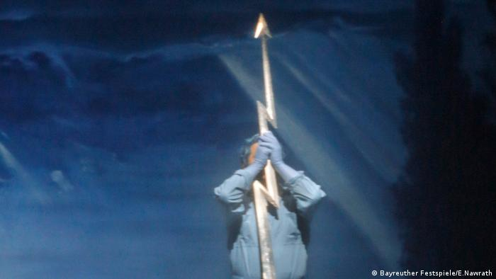 Man holds a spear in the shape of a lightning bolt before a pale blue backdrop