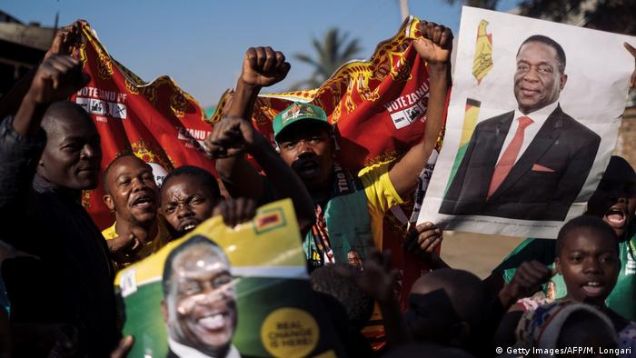 Cheering supporters hold up placards bearing Mnangagwa's image