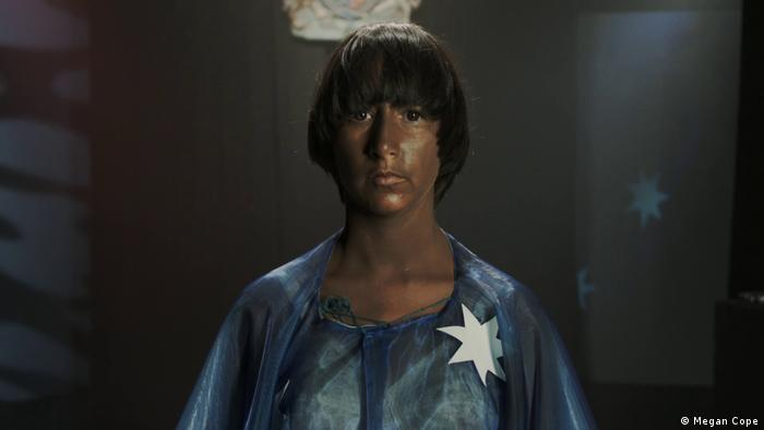 A still from Megan Cope's film The Blacktism showing a dark-skinned young man wearing a white star on his chest (Megan Cope)