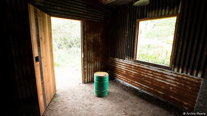 Interior of a wooden shack with a dirt floor (Archie Moore)