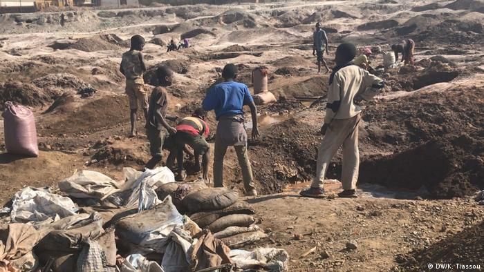 Einige Kinder und Männer stehen im Tagebau bei Kipushi