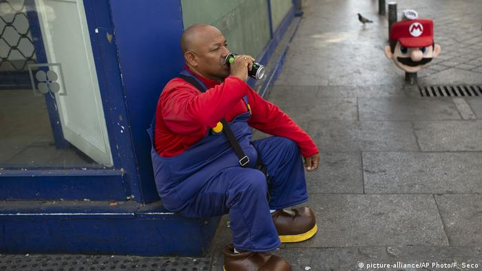 A man wearing a Mario Bros costume takes a break from work posing for tourist photos in the shade at Sol square in Madrid, Spain