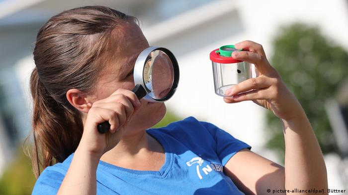 A girl looking through a magnifying glass at an insect in a jar
