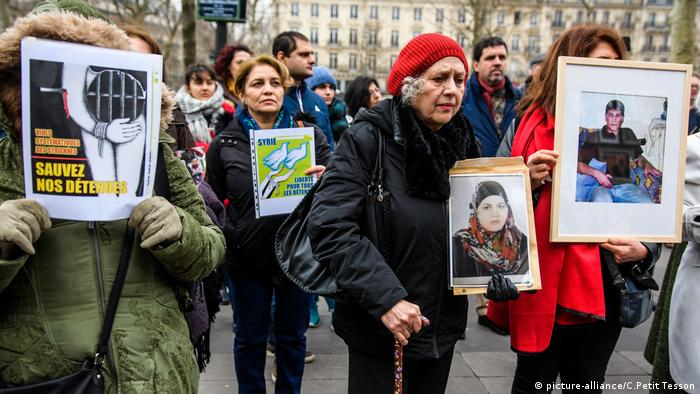 Women hold pictures of missing Syrians