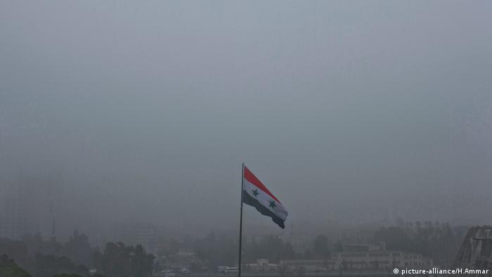 A Syrian flag waves in heavy fog
