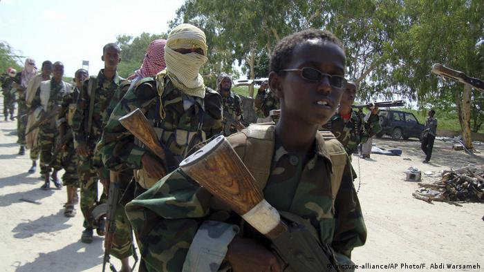 A young boy leads a group of al-Shabab fighters during a military exercise. They are all carrying weapons.