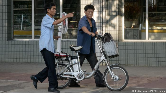 Two men push an electric bicycle carrying an electric fan along a street in Pyongyang, North Korea