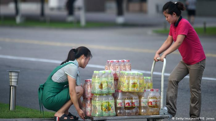 Women push a cart laden with North Korean soda drinks across a road in Pyongyang