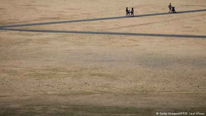 Visitors to Greenwich Park in London walk on the footpaths in between the dry brown grass