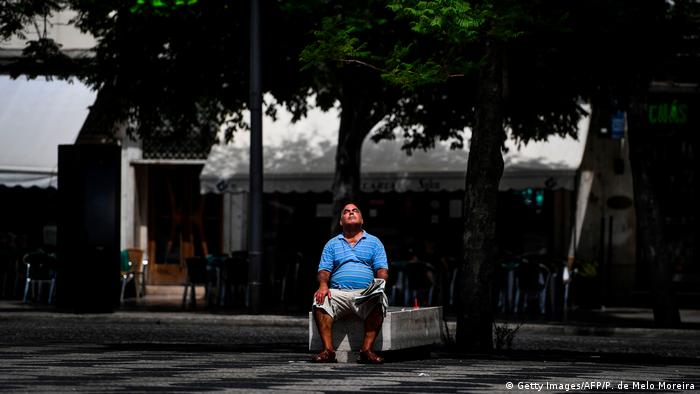 A man sitting on a park bench in Lisbon, Portugal