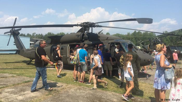 A US Army helicopter is surrounded by fairgoers