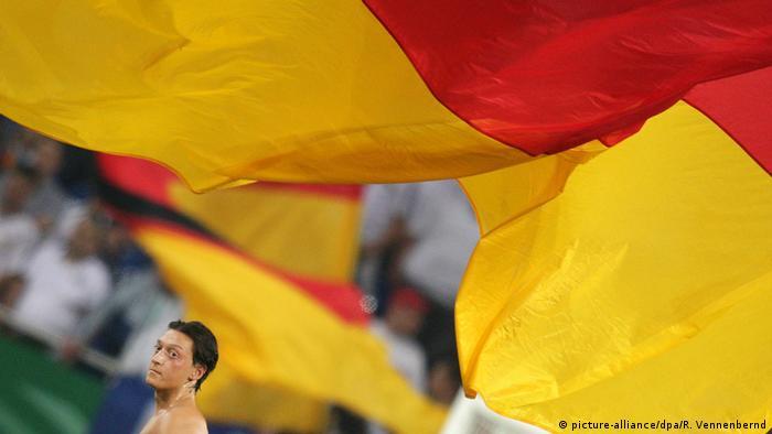 Mesut Özil, im Vordergrund eine Deutschlandflagge.