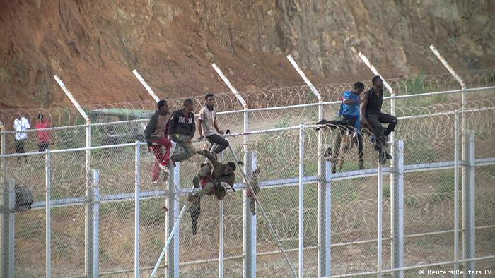 African migrants climb the border from morocco to Spain's North African enclave of Ceuta, Spain