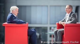 Seehofer and Thomas Baumann sit across from one another in red chairs (picture-alliance/dpa/G. Fischer)