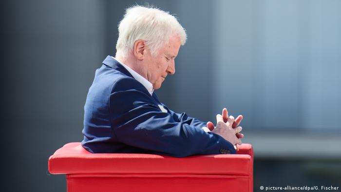 Seehofer sits in a chair with his hands crossed (picture-alliance/dpa/G. Fischer)