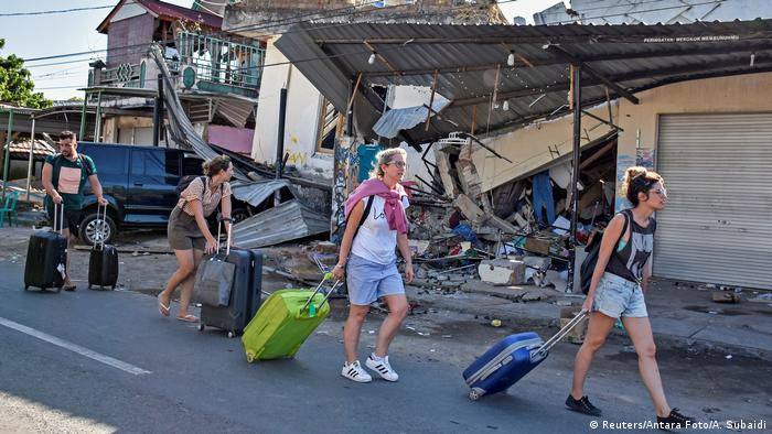 Foreign tourists pull their suitcases as they walk past damaged buildings
