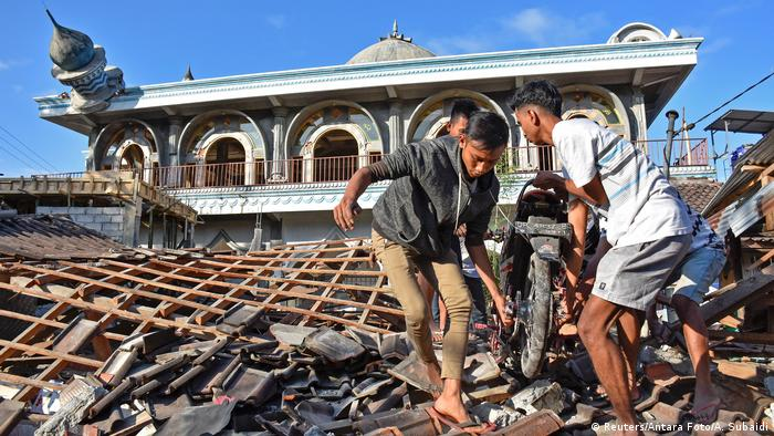 Men remove a motorcycle from a destroyed house after the Lombok earthquake (Reuters/Antara Foto/A. Subaidi)