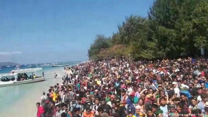 People crowd on the shore as they attempt to leave the Gili Islands
