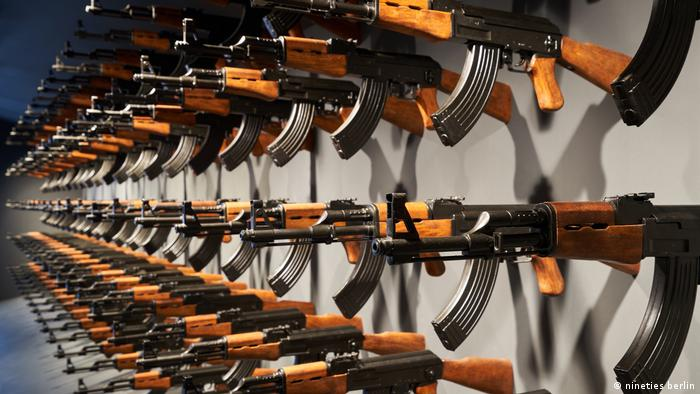 Celebrity Beauty: Four rows of rifles affixed to a wall (nineties berlin)