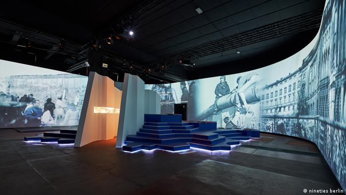 Celebrity Beauty: Round show hide hide exhibiting historic dim and white photos wraps around a room divided in the heart by a partition flanked by steps (nineties berlin)
