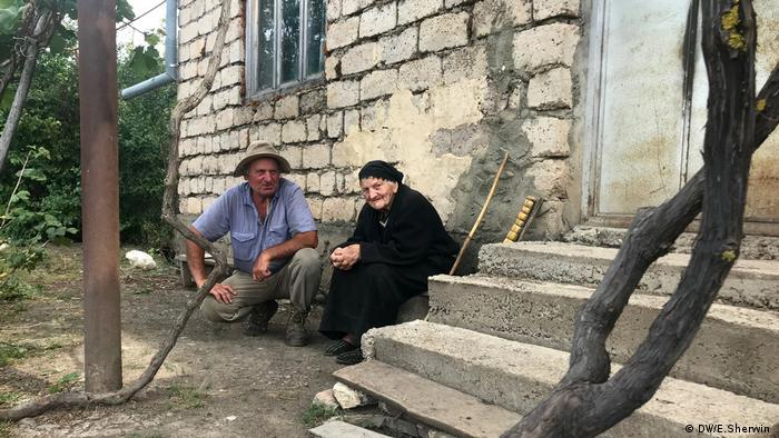 Two people sit by their home in the Georgian village of Ditsi