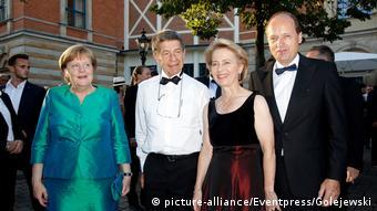 Angela Merkel in a shiny green gown and Ursula von der Leyen in black, posing with their husbands