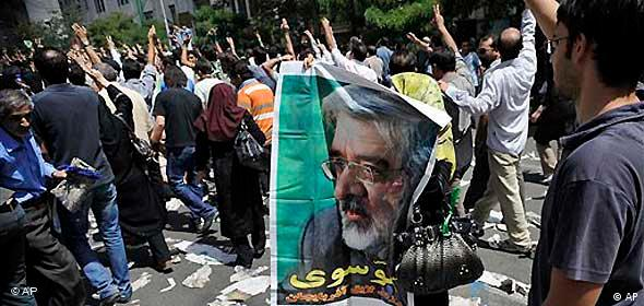 Protesters of the Iranian election march along the street holding a poster of Mir-Hossain Mousavi