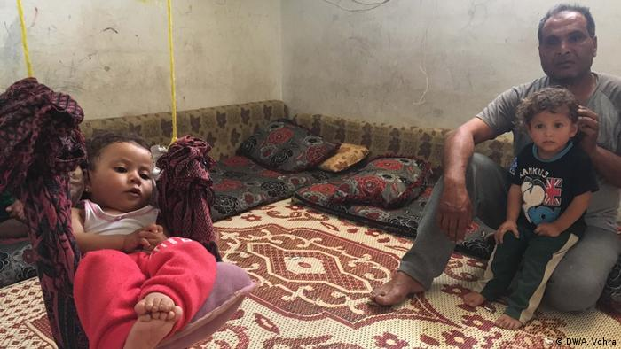 A man with his children in a refugee camp