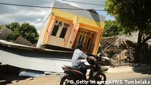 07.08.2018 TOPSHOT - A man riding a motorcycle passes by a damaged house at Sira village in northern Lombok in West Nusa Tenggara province on August 7, 2018, two days after the area was struck by an earthquake. - The shallow 6.9-magnitude quake killed at least 98 people and destroyed thousands of buildings in Lombok on August 5, just days after another deadly tremor surged through the holiday island and killed 17. (Photo by SONNY TUMBELAKA / AFP) (Photo credit should read SONNY TUMBELAKA/AFP/Getty Images)