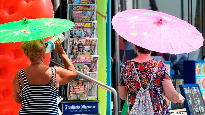 Two women with umbrellas in the sun in Spain
