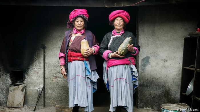 Two indigenous women in colorful dress hold pumpkins