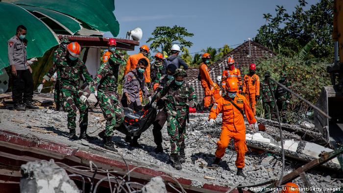 Indonesian soldiers and search and rescue teams carry the body of a victim