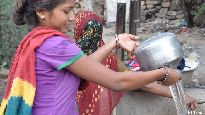 A woman fills up vessels at the water fountain