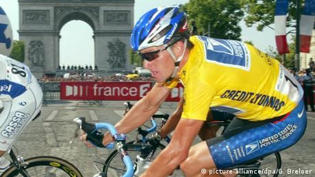 Lance Armstrong at the 2002 Tour de France, wearing the yellow jersey, riding past the Arc de Triomphe. (Photo: picture-alliance/dpa/G. Breloer)