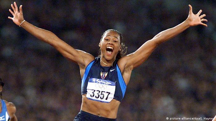 Marion Jones sprintet mit hochgerissenen Armen als erste über die Zielline im Olympiastadion von Sydney (Foto: picture-alliance/dpa/J. Haynes)