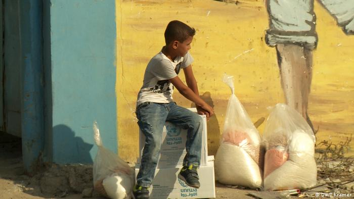 A boy sits with on boxes of food aid from UNRWA