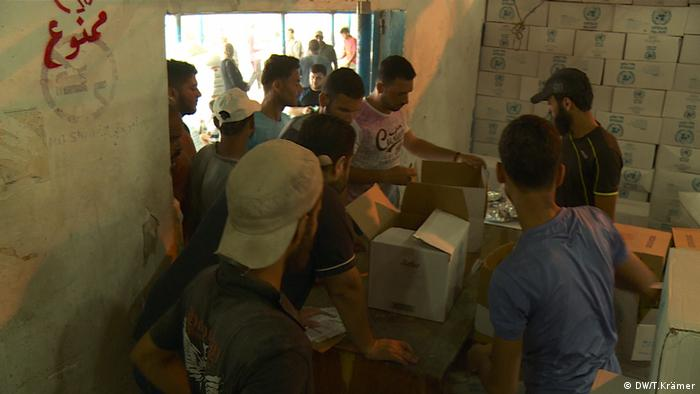 Palestinians in Gaza collect food aid at an UNWRA