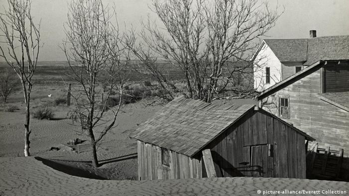 A Kansas farmhouse surrounded by sand dunes in 1936 (picture-alliance/Everett Collection)