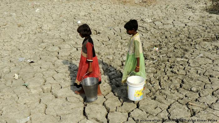 Children carrying water buckets across a dried out landscape