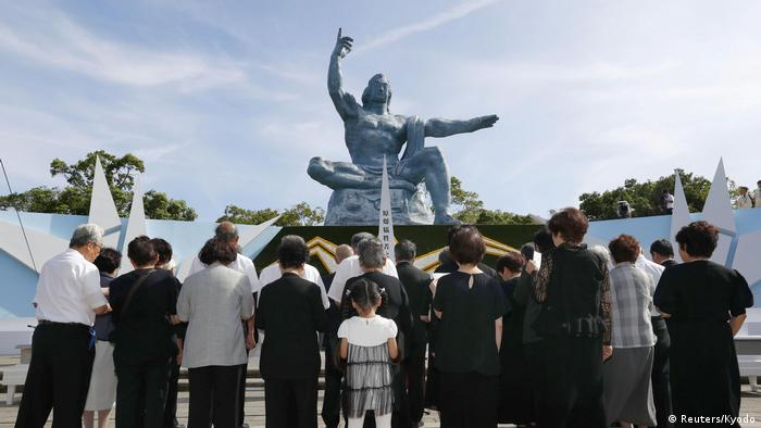 Survivors and children gather in front of the Peace Statue in Nagasaki