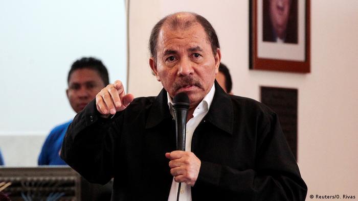 Daniel Ortega speaks into a microphone